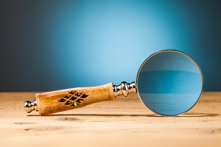 magnifying  glass  on wooden table and blue background photo