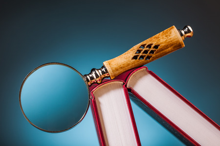 books on wooden table and magnifying glass  with blue background photo