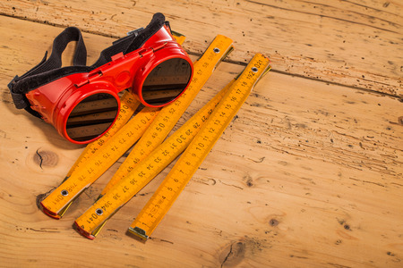 tool chuck: red safety goggles  and measure tool  on wooden table