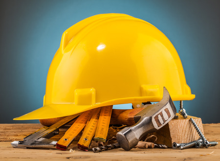 triplet: yellow helmet and wood mounting tools on wooden table Stock Photo