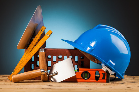 shrewd: blue helmet and builder tools on wooden table