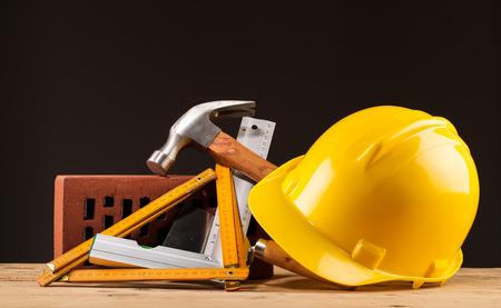 builder: casco de ladrillo y constructor herramientas de color amarillo en la mesa de madera