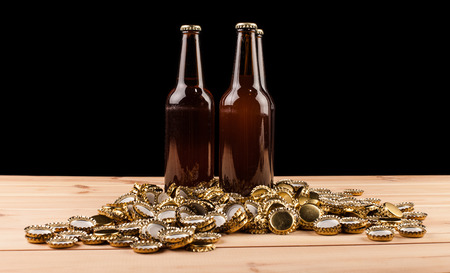 botellas de cerveza: bottles  of homemade beer  and bottle caps on table