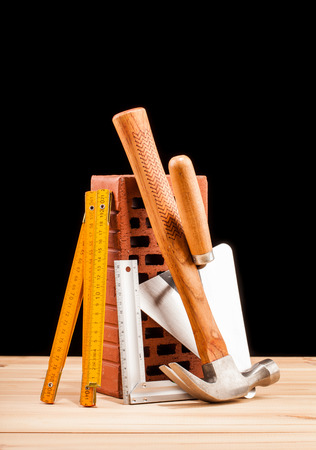 triplet: builder  tools on black background and wooden table Stock Photo