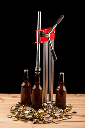 capping: bottles  of homemade beer  and bottle capping machine on table