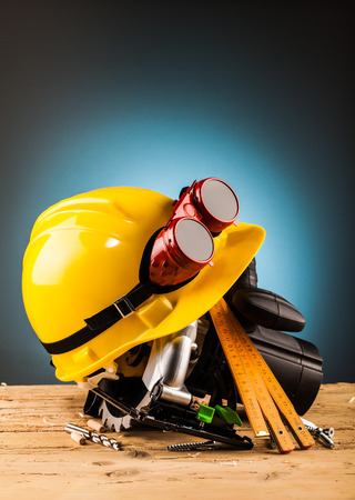 shrewd: yellow helmet and wood mounting tools on wooden table Stock Photo