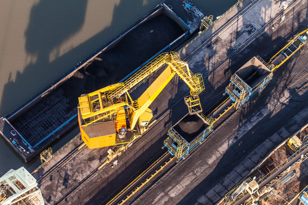 stacker: moving crane with a heap of coal next to the coal power plant in Wroclaw city in Poland