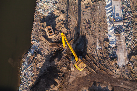 construction work: long arm excavator working on river bank in Poland