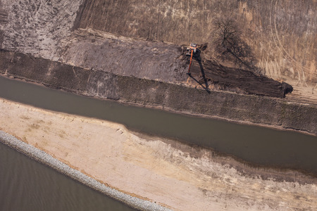 mine site: long arm excavator working on river bank in Poland