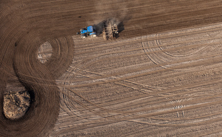 crop harvest: aerial view of harvest fields with tractor in Poland