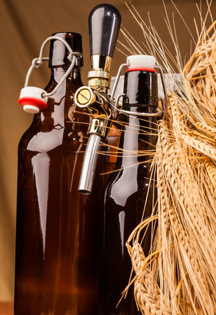 un bottled: bottle of light beer and spikes of barley on table Stock Photo