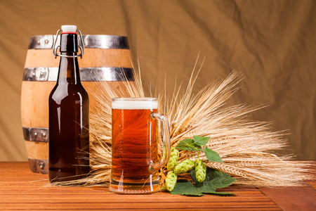 un bottled: Glass of light beer and spikes of barley on table