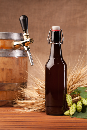 un bottled: beer bottle and spikes of barley on table