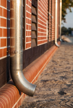 roofing system: gutter pipe and brick wall Stock Photo