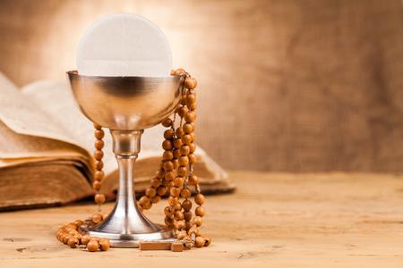 religion catolica: cáliz sagrada comunión en la mesa de madera