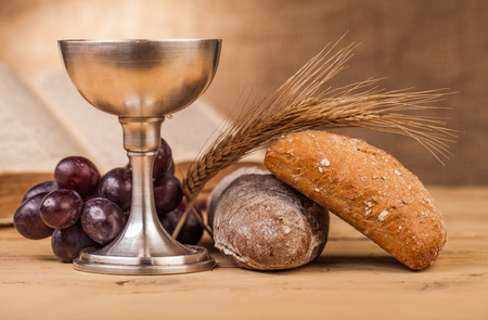 holy communion chalice on wooden table Imagens