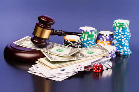 money risk: judge gavel and set of playing card with dices on reflective table