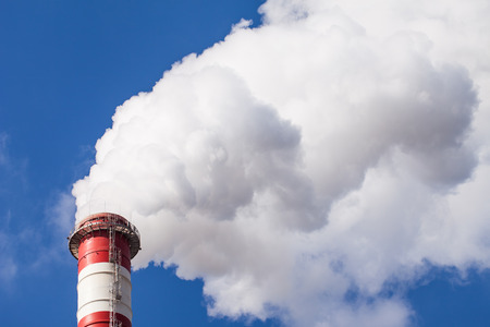 co2 emissions: Smoking chimney pollution on blue sky