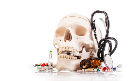 medicines human scull and drugs on table isolated on white