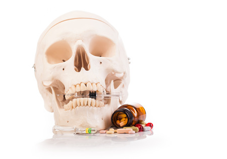 prescribed: medicines, human scull and drugs on table isolated on white Stock Photo