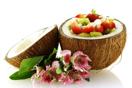 fresh fruit salad served in half coconut with flowers over white photo