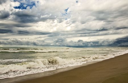 empty beach diring a storm with heavy clouds and waves photo
