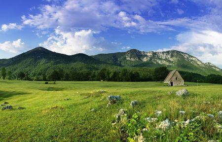 rural landscape with old house on the field over mountains  写真素材