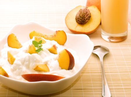 Yogurt with fresh peaches and mint for healthy breakfast. Light toning.