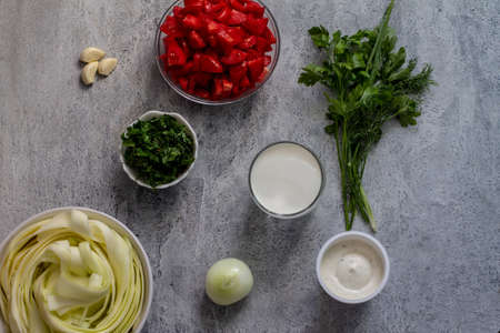 courgette pasta prepared raw ingredients courgette tomatoes cream cheese garlic and herbs Banque d'images