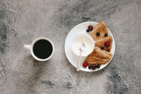 pancakes with fresh berries for breakfast and black coffee, flatlay Reklamní fotografie