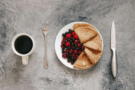 pancakes with fresh berries for breakfast and black coffee, flatlay