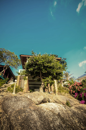 Small wood house is built on piles under rock. The summer sky of Koh Phangan, Thailand photo