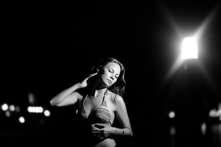 Young beautiful woman in bikini against night on beach near lantern photo