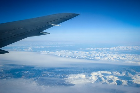 Wing of the plane on blue sky background and snowy mountains, view from window photo