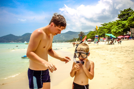father adjusting his sons snorkel and mask before swimming photo