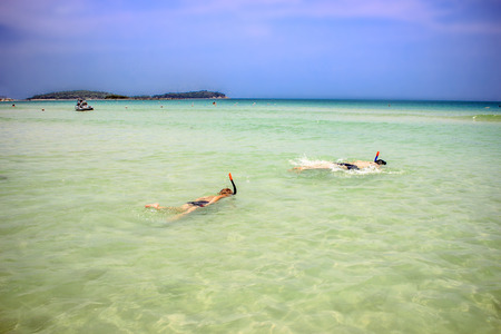 father and his son snorkeling with mask in the sea photo