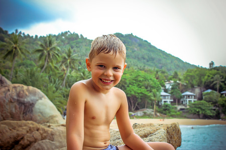 pre approval: childhood, travel, summer vacation, gesture and people concept. smiling little boy  over beach background