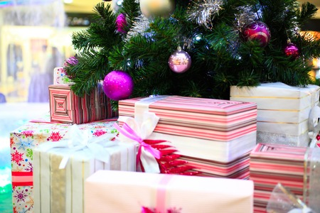 Close up of Decorated Christmas tree and boxes of gifts with bows photo