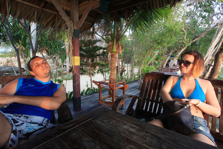 Young couple sitting and relaxing at a table on the beach. Koh Phangan photo