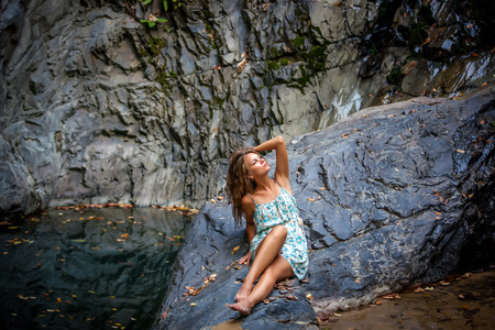 beautiful girl posing in dress at the waterfall photo
