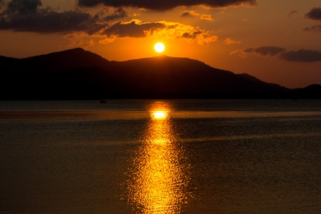samui: orange sunset at the sea with mountains silhouettes