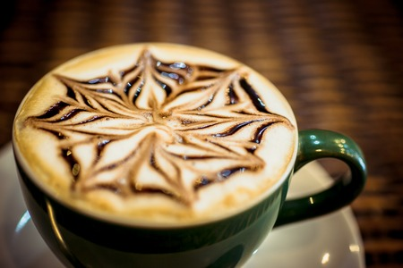 capuchino: Cup of coffee latte with design art in froth, on a wooden table. Close up macro