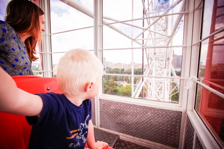 acrophobia: Mom and her son rolling on the Ferris wheel, look out window