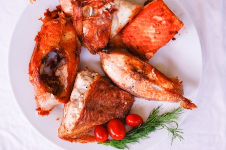 Tasty baked fish with cherry tomatoes and fresh herbs on plate photo