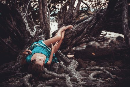 Beautiful young woman in a turquoise dress lying on roots of tree In the rainforest. Retro colors Stock Photo