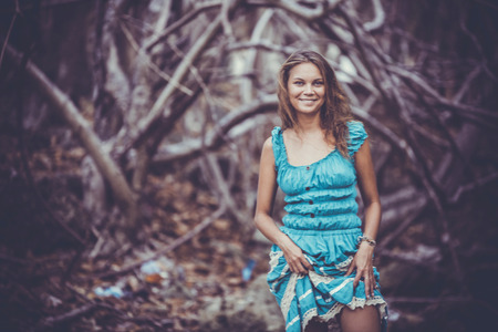 miracle leaf: Portrait of a beautiful young smiles woman in turquoise dress standing by trees In jungle forest