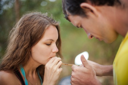 tolerate: Couple smoking a joint on nature