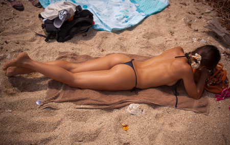 sunning: Beautiful young woman  lying and sunning on the beach