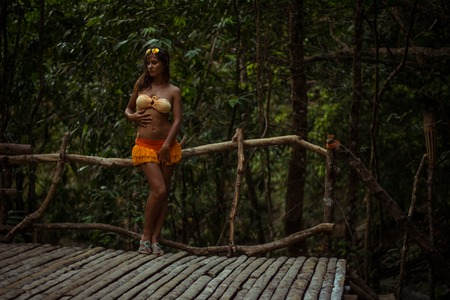 Woman posing on wooden floor background in forest photo
