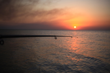 spinning reel: Fisherman sport hobby fishing rod or spinning reel on sea beach during sunset